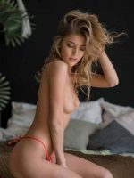 Ashley kneeling on her side fully nude with hand holding hair up.
