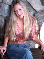 Charlotte sitting cross legged in blue jeans and multi colored shirt.