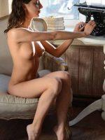 Cora sitting up fully nude while typing on old fashion typewriter.