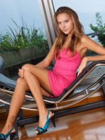 Gemma sitting in black chase lounge chair in pick dress.