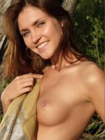 Hadley standing topless in woods holding cover over one breast.