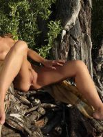 Hadley sitting on tree stump in woods completely nude spreading her legs.