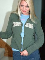 Inquild standing at base of stairs pulling zipper down of green sweat shirt.