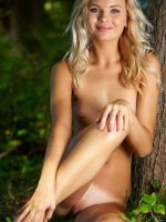 Jamie sitting on her side fully nude in front of tree.