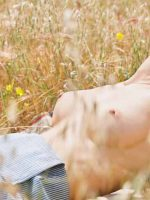 Mary laying back in the grass on her back topless.