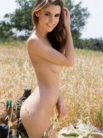 Mary kneeling on the grass at her side fully nude.