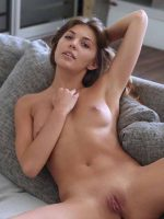 Maya laying back on couch fully nude with legs spread apart.