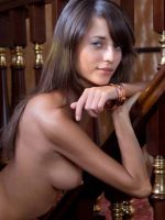 Naomi leaning over on baluster fully nude with hands crossed under chin.