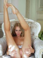 Olivia sitting in chair fully nude with legs raised into air.