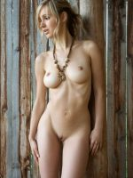 Ruby standing fully nude while leaning against barn wall with hands at her sides.