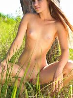Sydney squatting in grass fully nude with legs spread.
