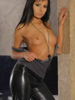 Viona standing against wall topless with hand above her head.